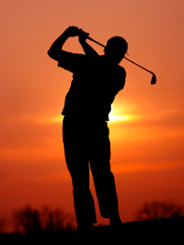 Golfer sunset swing